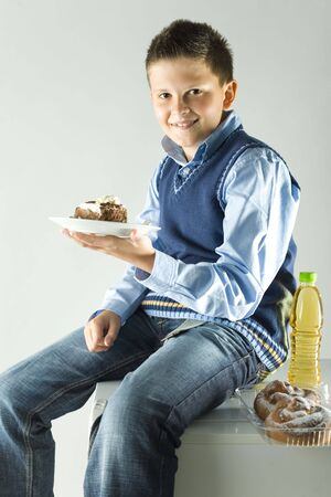 glutton: Smiling boy sitting on fridge and holding dessert plate with cake in hand. Looking at camera. Stock Photo
