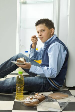 glutton: Boy sitting on the floor and eating cake. Side view. Looking at camera. Stock Photo