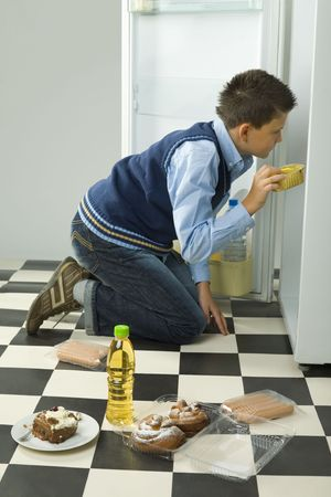 overeat: Young boy kneeling in front on the fridge and looking for something inside. Side view