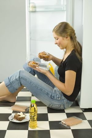 near side: Young woman eating the sweet bun. Shes sitting on the floor near by fridge. Side view.
