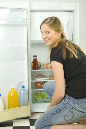 foodie: Young woman kneeling in front of the frige. Shes smiling and looking at camera. Stock Photo