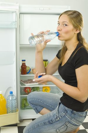 overeat: Young woman drinking mineral water in front of the fridge. Shes looking at camera. Side view