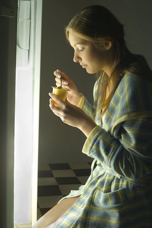 edibles: Young woman in front of the fridge eating yogurt. Side view. Stock Photo
