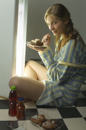 overeat: Young woman sitting in front of the fridge. Eating cake. Shes looking at camera. Side view. Stock Photo