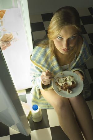 foodie: Young woman eating cake beside fridge.Shes looking at camera. High angle view.