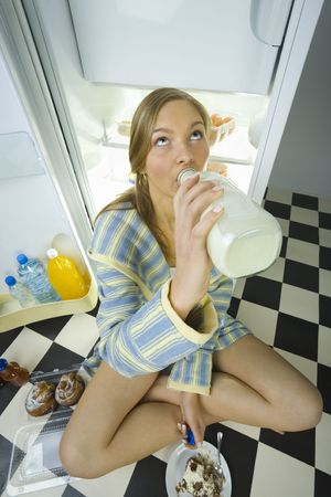 overeat: Young woman sitting by the fridge and drinking milk from bottle. High angle view.