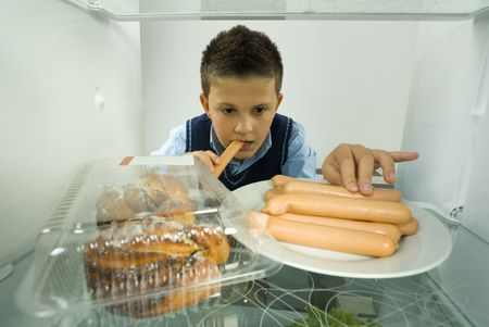 fatness: Young boy eating greedily weiners from fridge. Front view. Stock Photo