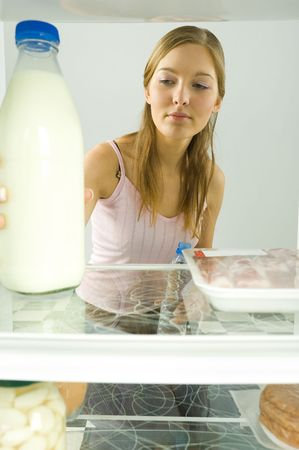 overeat: Young woman taking a bottle of milk from fridge. Front view.