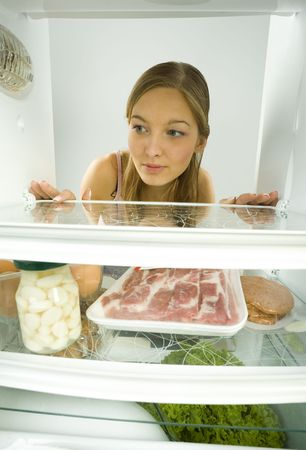 Young woman looking on empty shelf in fridge. Front view. photo