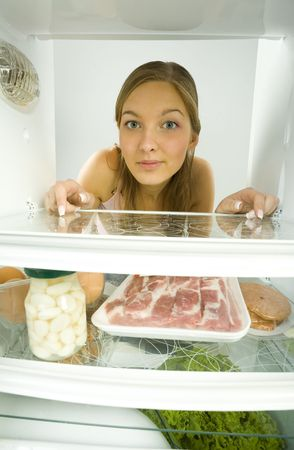eatables: Young woman looking at the camera from fridge. On one shelf lying for example meat and jar of marinated garlic. Front view