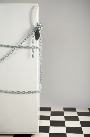 Closed fridge enwinded by chain and lock. Grey background. Front view photo