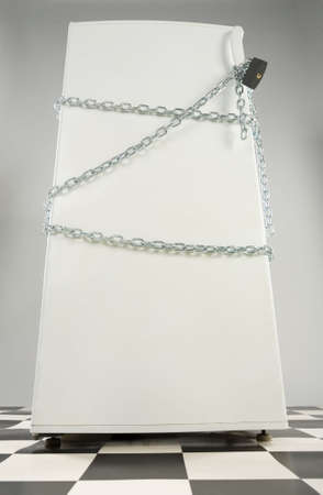 Closed fridge enwinded by chain and lock. Grey background. Low angle view. Stock Photo - 2606081