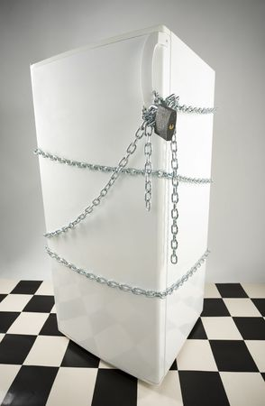 Closed fridge enwinded by chain and lock. Grey background. High angle view photo