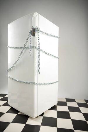 overeat: Closed fridge enwinded by chain and lock. Grey background. Side view Stock Photo