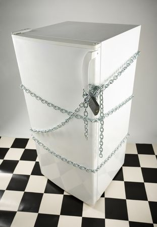 Closed fridge enwinded by chain and lock. Grey background. High angle view. photo