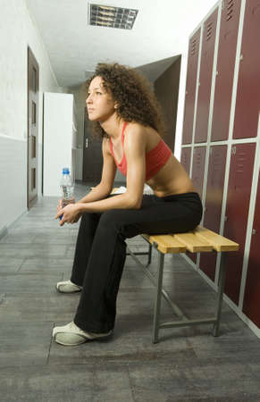 Young, tired woman sitting on bench in locker room. Holding bottle of water. Side view, whole body photo