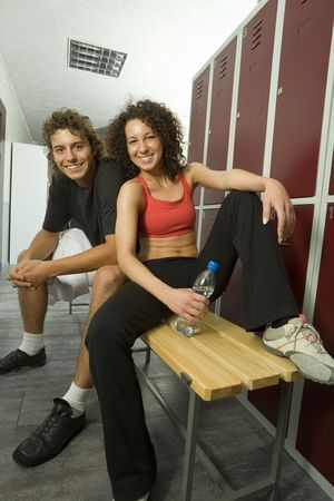 sportingly: Young couple, sitting on bench in gyms locker room. Smiling and looking at camera. Woman is holding bottle of water