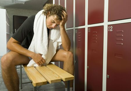 Young, exhousted man sitting on bench in locker room with closed eyes. Holding towel on neck. Front view photo