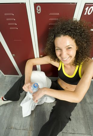 Young, tired but happy woman sitting on the floor in locker room. Holding bottle of water and towel. High angle view. Looking at camera photo
