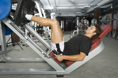 the whole body: Young man working out in gym. Lying and doing some kind of exercise. Side view, whole body Stock Photo