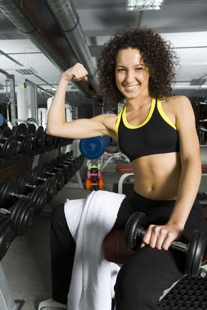 sportingly: Young woman showing hers muscles. Sitting in gym with dumbbell in one hand. Smiling and looking at dumbbell. Front view Stock Photo