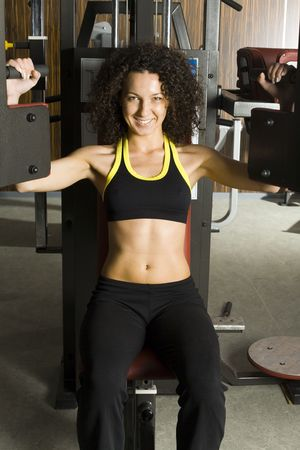 sportingly: Young woman working out in gym. Sitting and doing some kind of exercise. Smiling and looking at camera. Front view, whole body Stock Photo