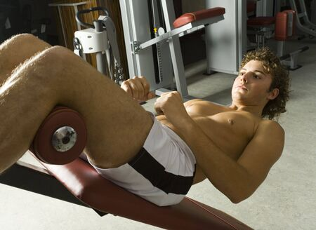 Young man with naked chest lying on bench and doing some kind of exercise. Side view photo