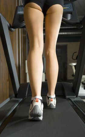 Legs of young woman, who is walking on track in gym. Rear view Stock Photo - 2607025