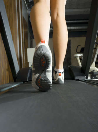 Legs of young woman, who is walking on track in gym. Rear view Stock Photo - 2607023
