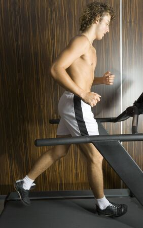 Young man with naked chest running on track in gym. Whole body, side view Stock Photo - 2607352