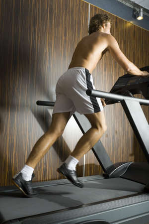 Young man without shirt running on track in gym. Whole body, rear view Stock Photo - 2607363