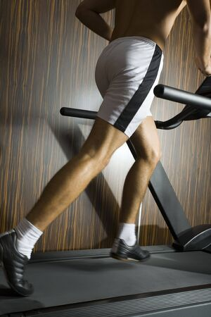 Young man with running on track in gym. We don't see his face. Side view Stock Photo - 2607349