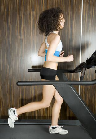 Young woman running on track in gym. Whole body, side view Stock Photo - 2607335