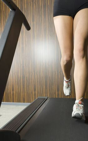 sportingly: Legs of young woman, who is running on track in gym. Front view