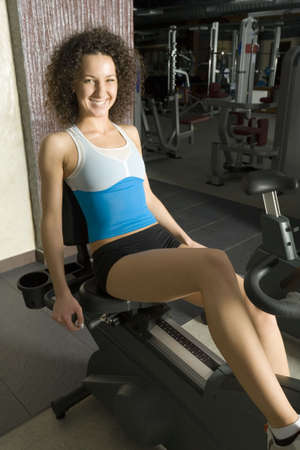Young woman working out in gym on bike. Smiling and looking at camera. Side view Stock Photo - 2607340