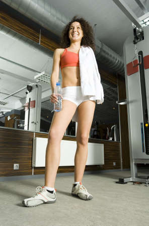 Young woman standing in gym with bottle of water and towel. Smiling and looking at something. Whole body, low angle view Stock Photo - 2607278