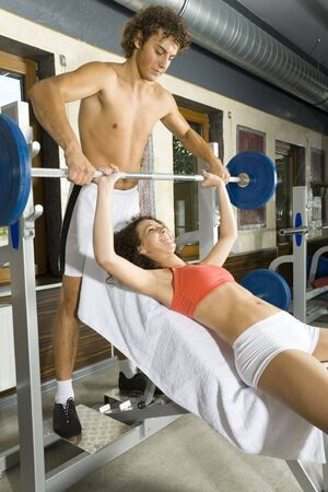 Young couple, working out in gym. Man is helping woman. Woman is lying on bench and picking up dumbbell. Smiling and looking at man. Side view Stock Photo - 2607412