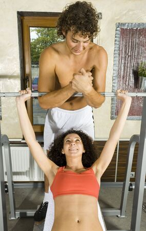 Young couple, working out in gym. Man is helping woman. Woman is lying on bench and picking up dumbbell. Smiling and looking at man. Front view Stock Photo - 2607398