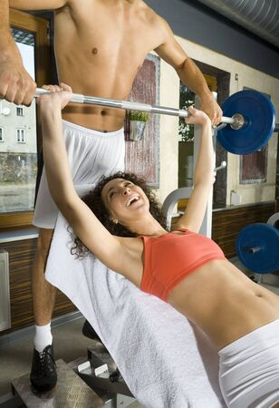Young couple, working out in gym. Man is helping woman. Woman is lying on bench and picking up dumbbell. Smiling and looking at man. Side view Stock Photo - 2607405