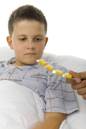 Young boy looking at yellow tablets. Hes lying in the bed. White background