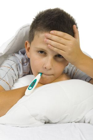 Young boy lying on bed with thermometer in mouth. Looking at camera. White background photo