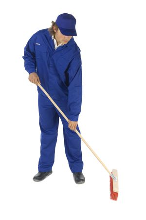 Young sweeping man in blue workwear. Isolated on white background Stock Photo