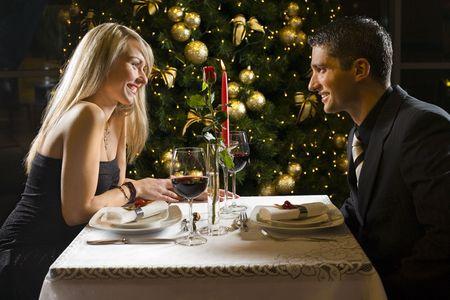 diner romantique: Couple au restaurant de la soir�e. Ils cherchent l'un vers l'autre et souriant.
