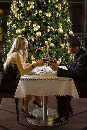 Couple at restaurant on dinner party. Theyre looking at each other and smiling. Stock Photo