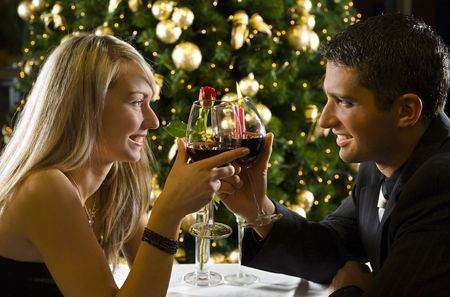 Couple at restaurant on dinner party. Theyre looking at each other and raise a toast.