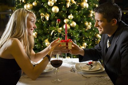 Couple at restaurant on dinner party. They giving each other a present. Stock Photo - 2651683