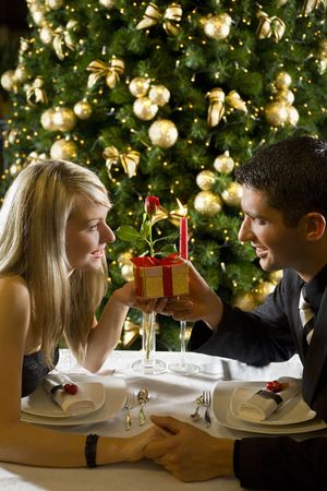Couple at restaurant on dinner party. They giving each other a present. photo