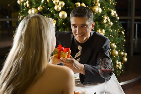 Couple at restaurant on dinner party. They giving each other a present. Focused on him. photo