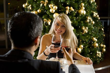 Couple at restaurant on dinner party. Theyre looking at each other and raise a toast. Focused on her.