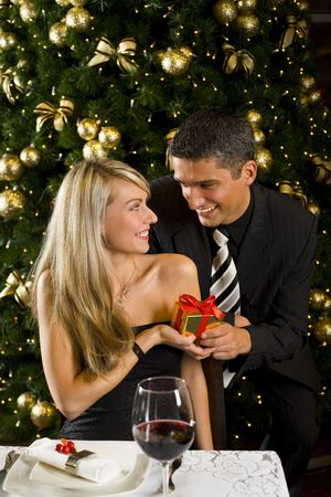 Couple at restaurant on dinner party. They giving each other a present. Front view. photo